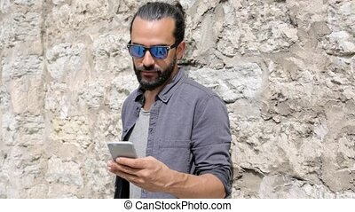 man texting message on smartphone at stone wall 2