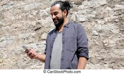 man texting message on smartphone at stone wall 6