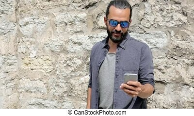 man texting message on smartphone at stone wall