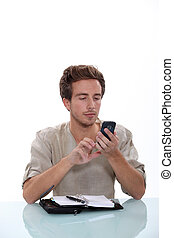 Man texting on his cellphone with an open diary on a white desk
