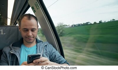 Man texting on his smartphone while travelling by train -...
