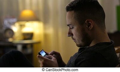 Man texting, sending sms on smartphone on sofa at night