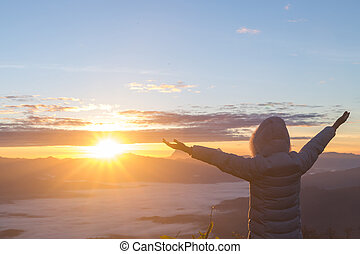 Man thank God on the mountain at sunrise in the morning