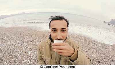 man, that looks funny, drinking coffee on the beach