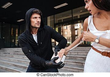 Man thief in black hoodie stealing woman bag on the street