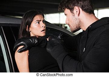 Man thief threatening with gun to scared woman near car - ...