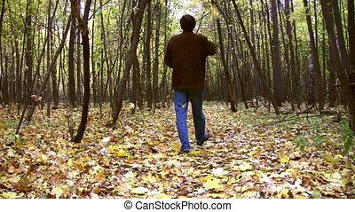 man throw leaves in autumnal wood - Man throw leaves in...