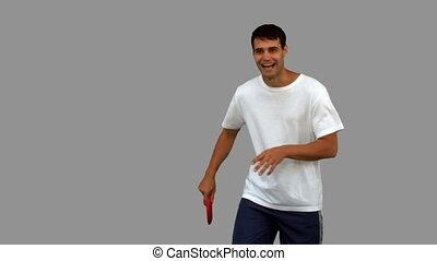 Man throwing a frisbee on grey screen