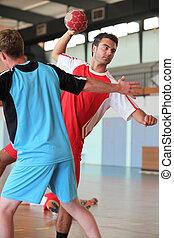 Man throwing ball during handball game