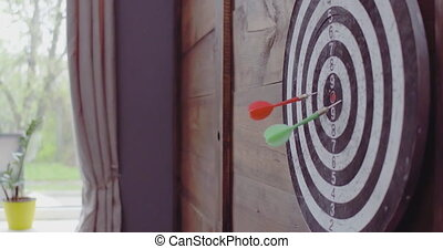 Man throwing dart in to a dart board hanging on classical ...