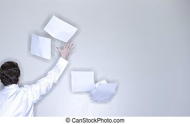 rear view of single man in white shirt raising his arm releasing stack of paper