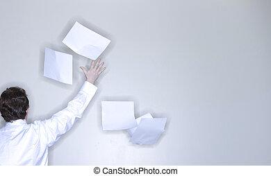 man throwing paper - rear view of single man in white shirt...
