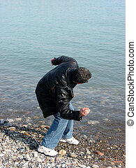 Man throwing pebbles - A man throwing pebbles into water on...