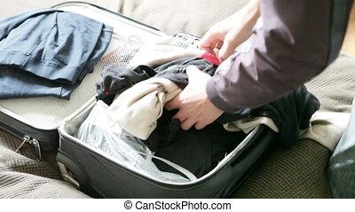man thrown clothes and toothbrush in suitcase and pulled out of it
