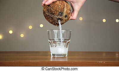 Man throws ice into a glass, then pours coconut water. Against the background of the lights