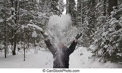 man throws up snow in the wood. Slow motion