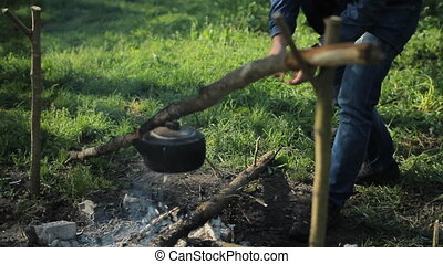 Man throws wood on the fire in the camping. Early morning in the forest