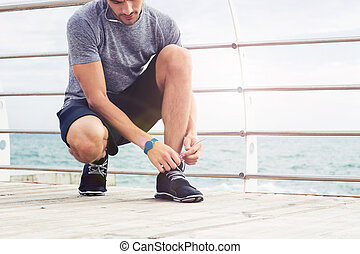 Man tie shoelaces outdoors