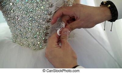 Man tieing lace on wedding dress closeup