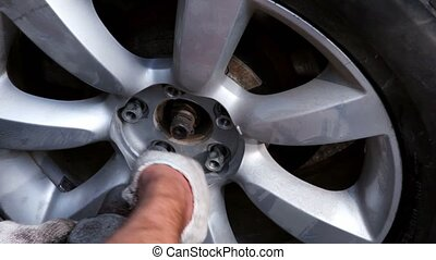 Man tight nuts on car wheel by automatic screwdriver