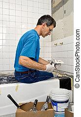 Man Tiling A Bathroom Wall - Man applying ceramic tile to a...