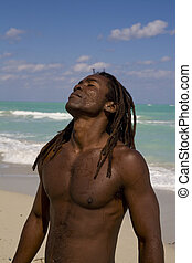 black man tilting his head behind on the beach over blue sea and blue sky