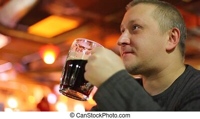 Man to drink beer, indoor.