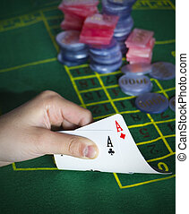 Man to look at two cards in his han
