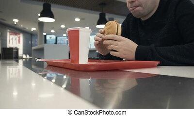 man tongue licks his mouth before eating a hamburger or...