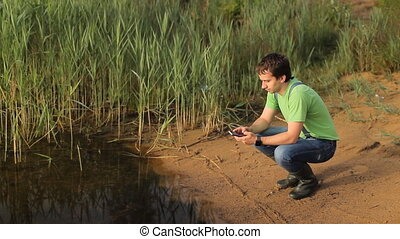 Man touch phone on the lake. Beautiful beach with sand and grass