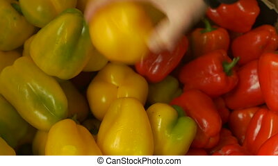 man touches, feels and chooses fresh sweet bell pepper in...
