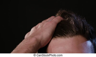 Man Touching his Hair Against a Black Background