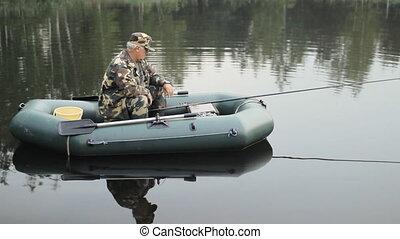 Man touching smart watches on the lake. A fisherman with a fishing rod on the inflatable boat