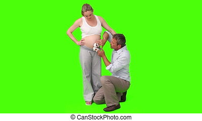 Man touching the belly of his pregnant wife with little shoes