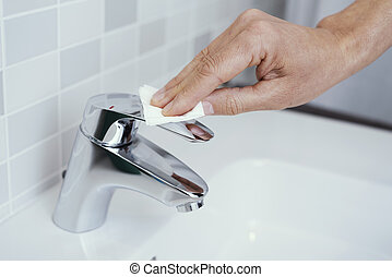 man touching the faucet with a piece of paper