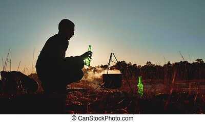 man tourist are beer sitting by bonfire party in nature...