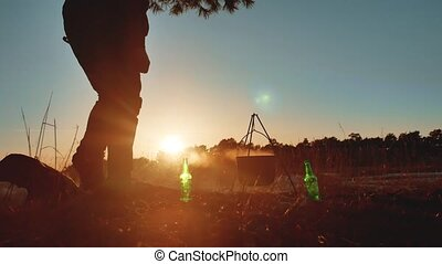 man tourist are sitting by bonfire party in nature camping silhouette sunlight sunset. man silhouette on vacation cauldron lights fire bonnet sausages and drink beer outdoors lifestyle