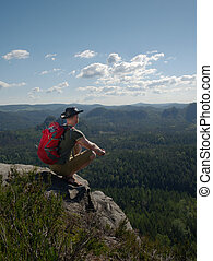 Man tourist at top of mountain during a hike in summer.