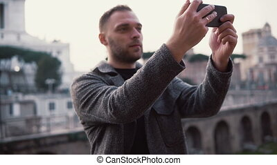 Man tourist explores new city, takes selfie photos of city centre on the smartphone. Male enjoys trip to Rome, Italy.