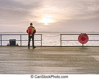Man tourist in autumn mist on wooden pier above sea.