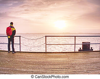 Man tourist in autumn mist on wooden pier above sea