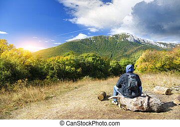 Man tourist in mountains forest. Leisure activity.