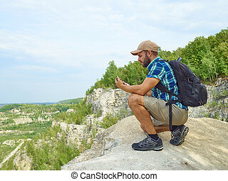 Man tourist is using a smartphone while sitting on the edge of a cliff in the mountains.