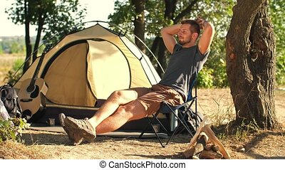 Man tourist resting on chair in front of tent - Young man...