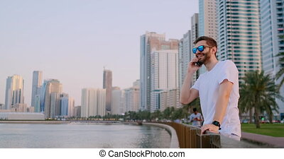 Man tourist standing on the waterfront talking on the phone listening