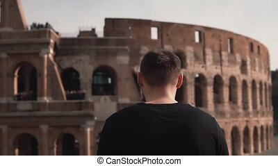 Man tourist stands at Colosseum in Rome, Italy. The handsome male takes smartphone, serves the internet. Slow motion.