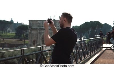 Man tourist takes photos of landscapes in Rome, Italy on smartphone. The Konstantin s arch on background. Slow motion.