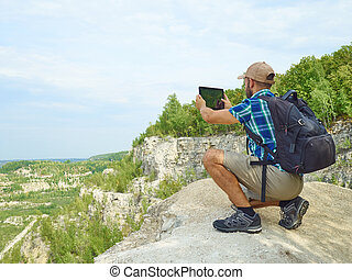 Man tourist uses tablet computer sitting on the edge of a cliff in the mountains.