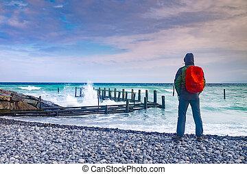 Man tourist watch how waves crash into pier - Man tourist ...