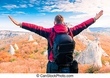 Man Tourist with a backpack with open arms enjoying the autumn landscape in the mountains